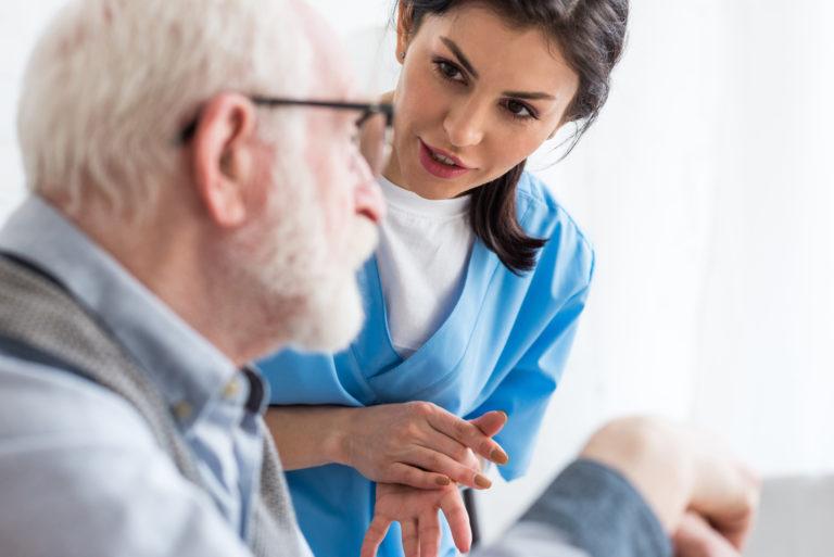 Undersköterska talar med patient